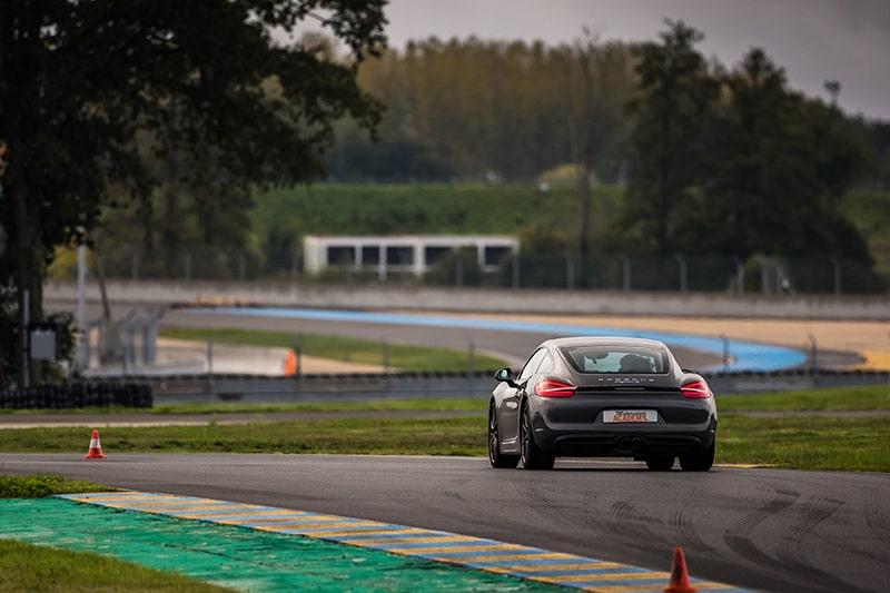 Porsche Cayman S sur le Circuit du Mans vu de derrière
